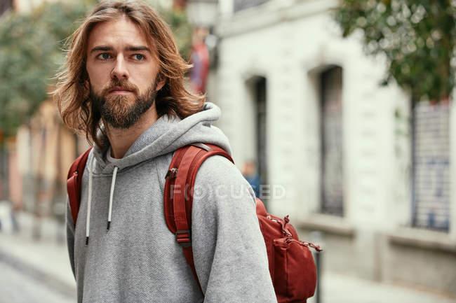 Молодий бородатий вродливий чоловік у сірому капюшоні з рюкзаком. — стокове фото