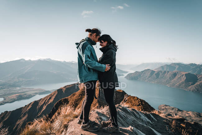 Embracing couple of romantic happy tourists standing in peak of mountain looking at landscape of majestic valley in sunlight — Stock Photo