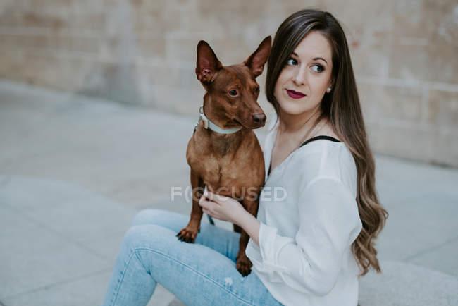 Donna casuale con cane mastino seduto su un gradino di cemento sulla strada e guardando altrove — Foto stock