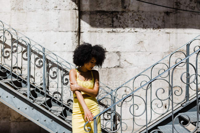 African American woman in yellow suit standing near railing and looking down on urban background — Stock Photo