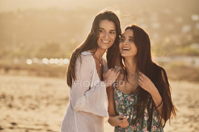 Cheerful adult brunette women in summer light dresses on sandy beach at the golden hour — Stock Photo