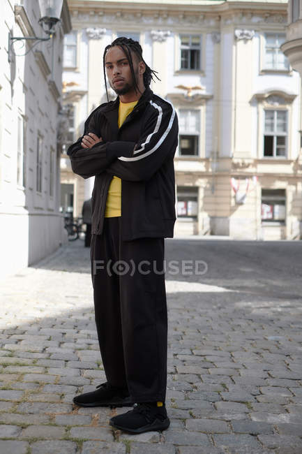 Young ethnic man with braided hair wearing black sports suit looking at camera on urban background — Stock Photo