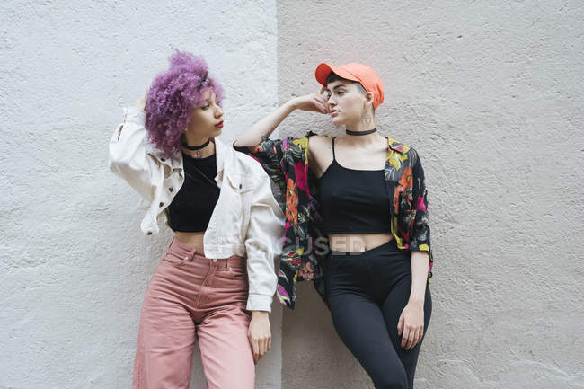 Girlfriends leaning on wall posing side by side together and looking at each other — Stock Photo