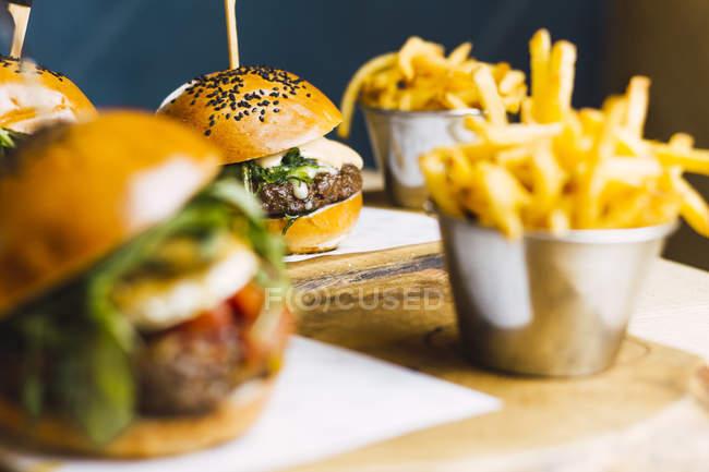 Jugosas hamburguesas deliciosas y papas fritas en la mesa de madera - foto de stock