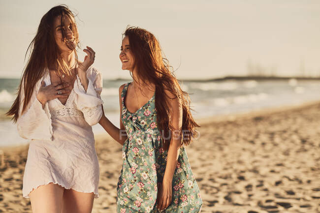 Cheerful adult brunette women in summer light dresses on sandy beach at the golden hour — Stock Photo