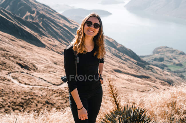 Cheerful fit woman in black outfit and with backpack standing on landscape with mountain valley looking at camera — Stock Photo