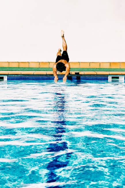 Молодий чоловік стрибає до басейну. — стокове фото