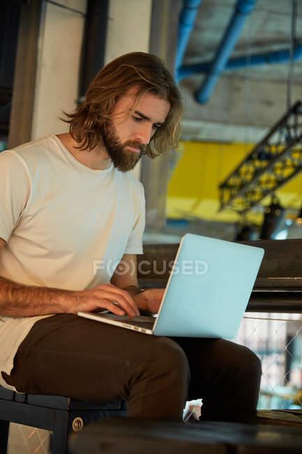 Молодий бородатий гарний чоловік сидить і працює на ноутбуці. — стокове фото