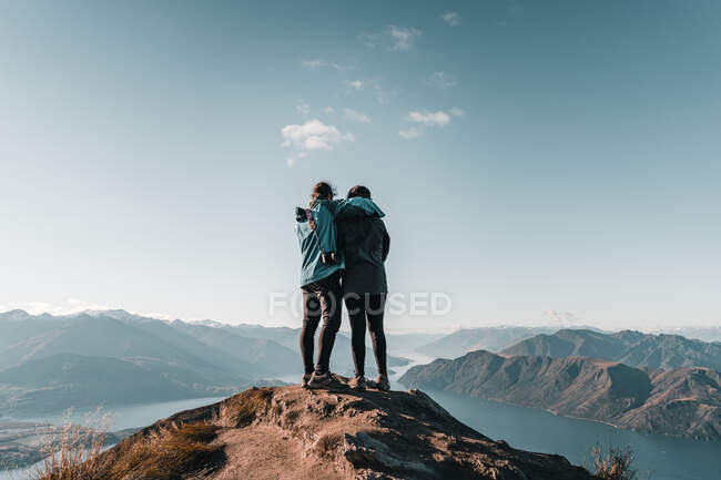 Back view of embracing happy tourists standing in peak of mountain looking at landscape of majestic valley in sunlight — Stock Photo