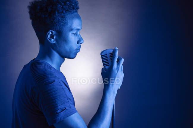 Африканский молодой человек держит винтажный микрофон в синем свете — стоковое фото