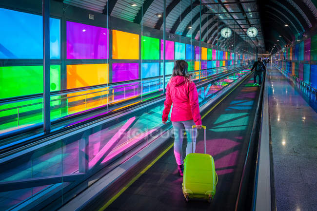 Unrecognizable woman with suitcase riding mowing walkway near colorful panels inside Madrid Barajas Airport in Spain — Stock Photo