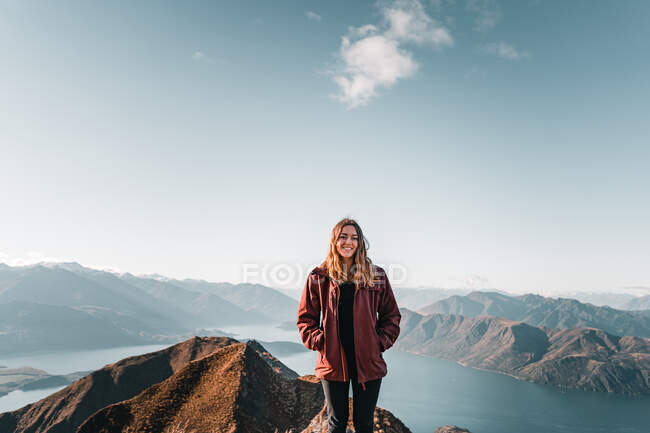 Smiling woman in coat standing on high peak of mountains in range smiling and looking at camera — Stock Photo