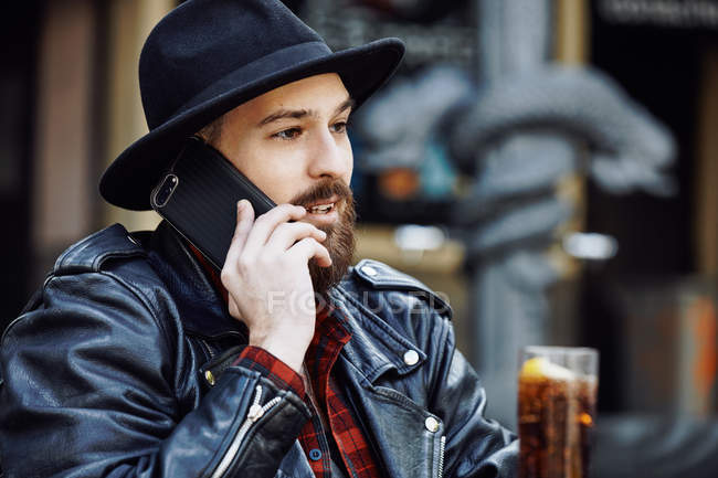 Young bearded handsome man in black hat and leather jacket talking on mobile phone in outside cafe — Stock Photo