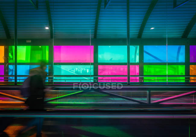 Blurred person with suitcase on mowing walkway near colorful panels inside Madrid Barajas Airport in Spain — Stock Photo