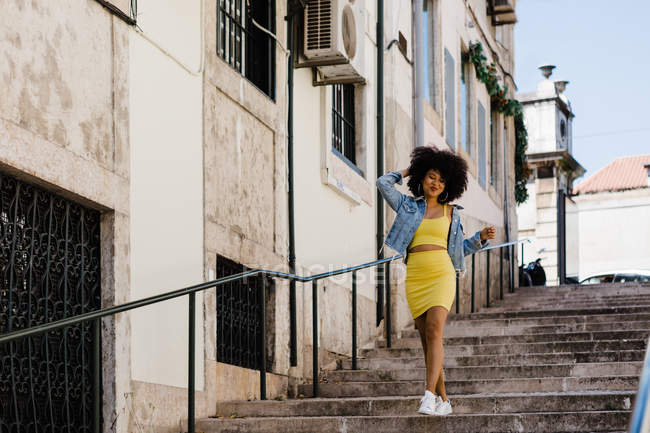 African American woman in yellow suit and denim jacket walking downstairs and looking at camera on urban background — Stock Photo