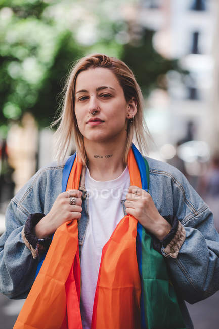 Girl with face tattoo and LGBT flag looking at camera while standing on blurred background of city street — Stock Photo