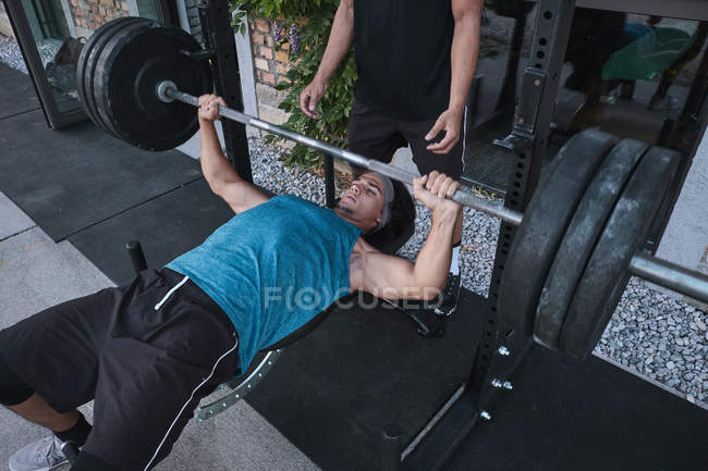 From above young guy exercising with barbell with help of unrecognizable trainer during training in outdoor gym — Stock Photo