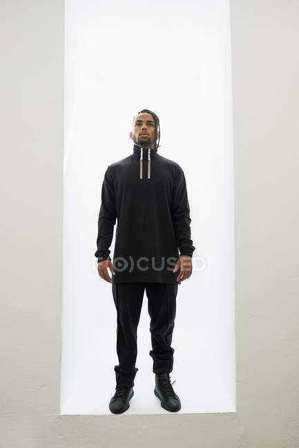 African American man in black clothes with braided hair standing isolated on white background — Stock Photo