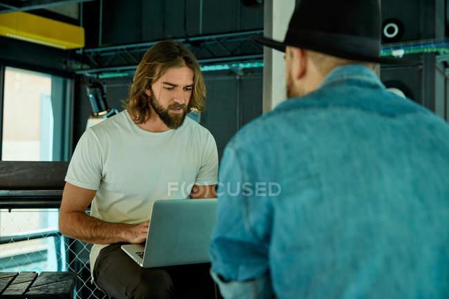 Giovani uomini barbuti bello sul serio e concentrati lavorando digitando su computer portatile sulle ginocchia — Foto stock