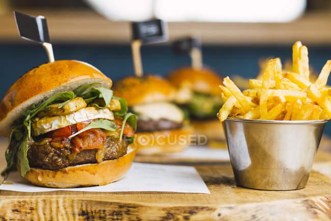 Jugosa hamburguesa deliciosa y patatas fritas en la mesa de madera - foto de stock