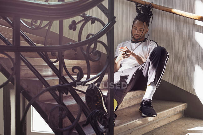 Handsome African American man with braided hair sitting on stairs and looking at hands — Stock Photo