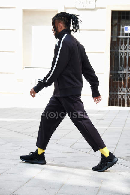 Side view of African American man with cornrows in black sports suit walking on urban background — Stock Photo