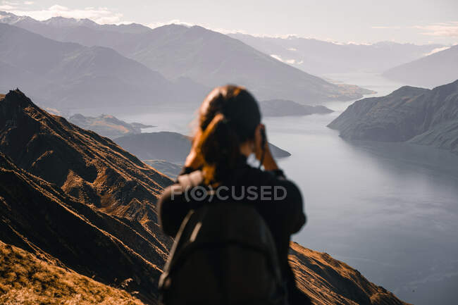 Back view of woman in blur standing on high peak and taking photo of amazing panorama with lake in sunlight — Stock Photo