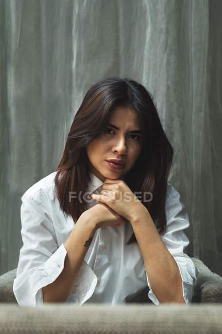 Серьезная молодая женщина в белой рубашке сидит на диване — стоковое фото
