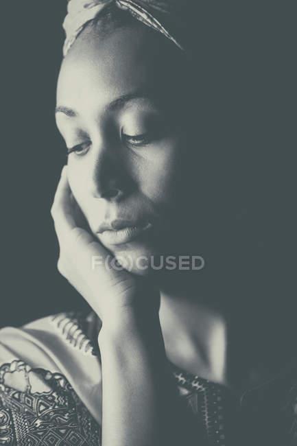 Молодая африканская женщина в этнической одежде и тюрбане на голове, опираясь на руку — стоковое фото