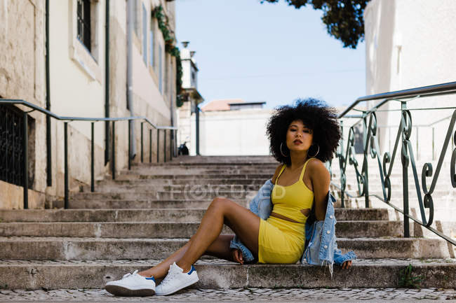 African American woman in yellow suit and denim jacket looking at camera while sitting on stairs on urban background — Stock Photo