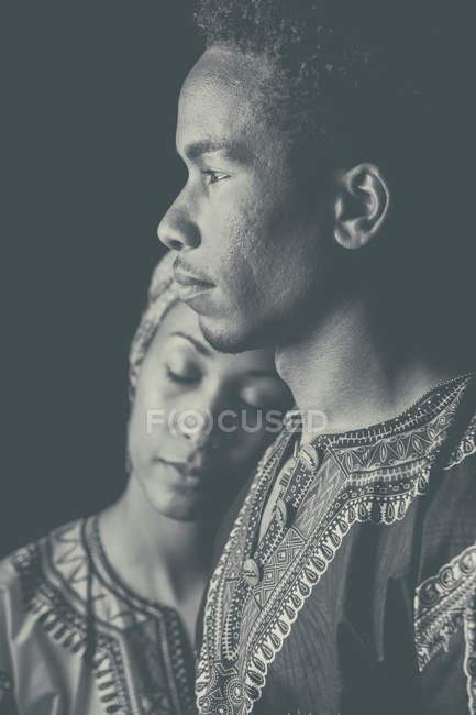 Крупный план молодой привлекательной африканской пары в этнической одежде стоя и сближаясь — стоковое фото
