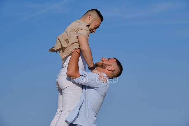 Vista laterale di felice gay uomo sollevamento fino e andando a bacio fidanzato su deserto spiaggia su estate — Foto stock