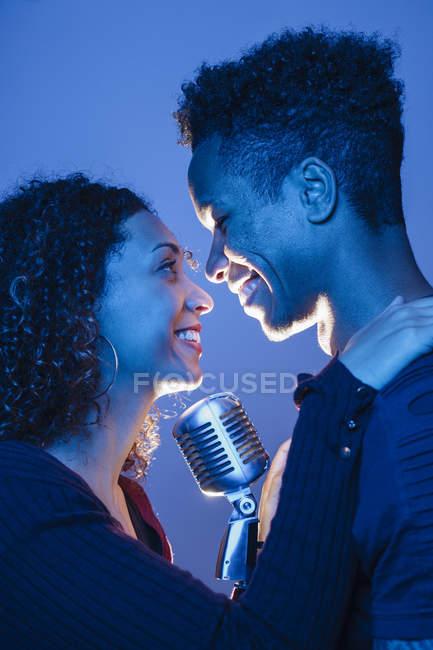Улыбающаяся молодая африканская пара держит винтажный микрофон и обнимается в синем свете — стоковое фото