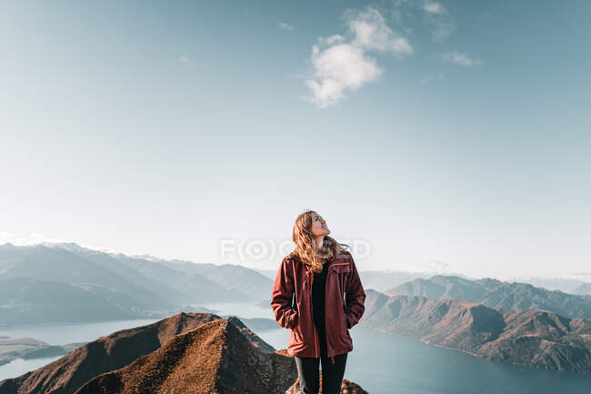 Smiling woman in coat standing on high peak of mountains in range smiling and looking at the sky - foto de stock