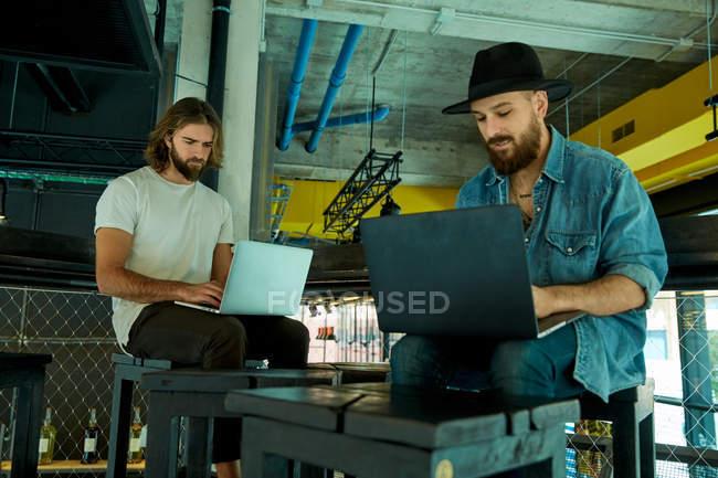 Giovani uomini barbuti bello seriamente e concentrati lavorando digitando su computer portatili sulle ginocchia — Foto stock