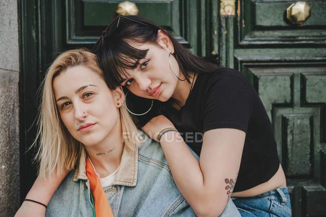 Молодая женщина обнимает подругу, сидя у входа в здание на городской улице — стоковое фото