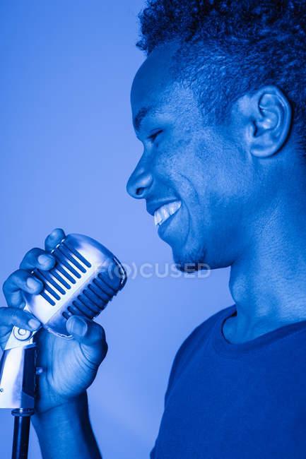 Nahaufnahme eines glücklichen afrikanischen jungen Mannes, der sein Mikrofon im Blaulicht hält — Stockfoto