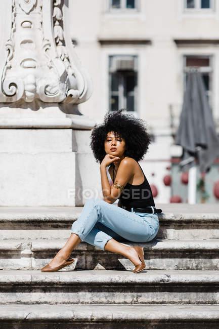 Ethnische Frau in Jeans und Tank-Top entspannt sich und sonnt sich auf Steintreppen vor urbanem Hintergrund — Stockfoto