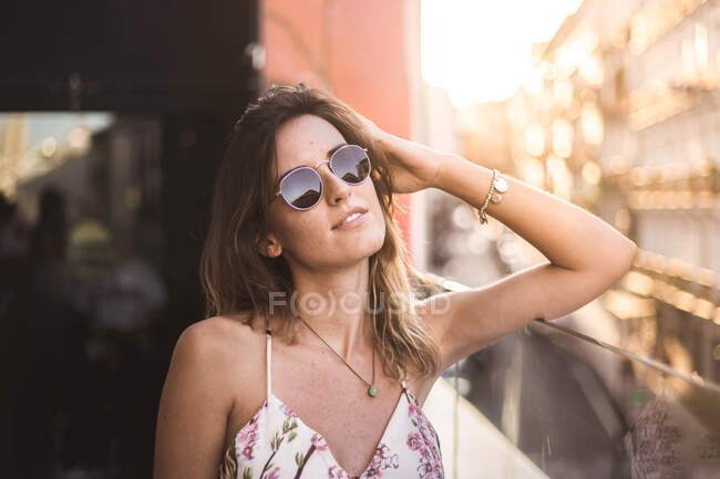 Attractive pensive model with long hair in summer dress on blurred background using sunglasses — Stock Photo