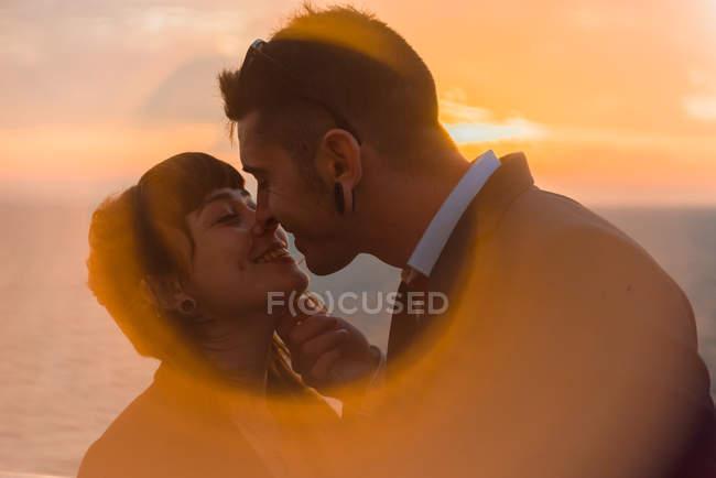 Vista lateral do casal jovem romântico se ligando e beijando em luz do pôr do sol suave no navio em mar calmo — Fotografia de Stock