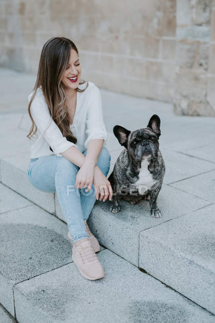 Casual young woman sitting on concrete pavement with bulldog and smiling — Stock Photo