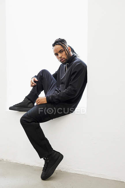 African American man in black clothes with braided hair sitting isolated on white background — Stock Photo