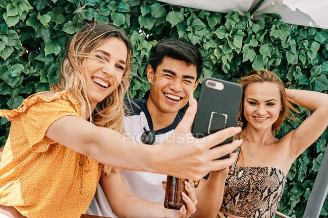 Dos mujeres y un hombre bebiendo cerveza y tomando selfies - foto de stock