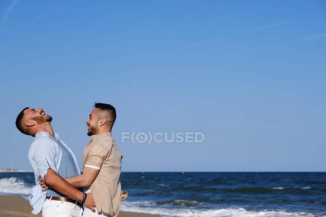 Вид сбоку веселый гомосексуалист поднимает счастливого парня с протянутыми руками на фоне голубого неба — стоковое фото