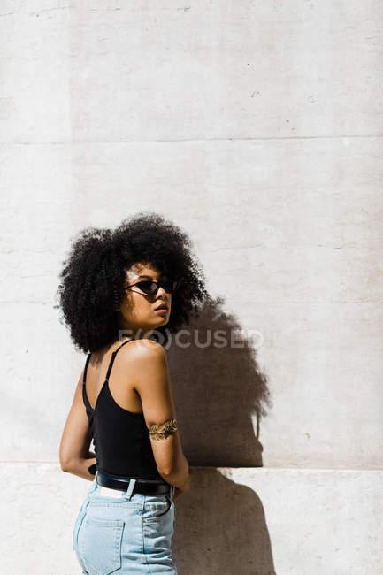 Joven mujer étnica en jeans y camiseta apoyada en la pared y mirando a la cámara al aire libre - foto de stock