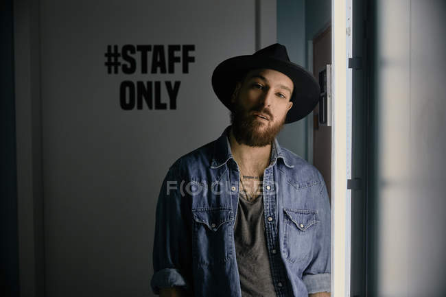 Young bearded handsome man in hat and denim shirt smiling and looking at camera in dark room — Stock Photo