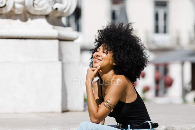 Smiling ethnic woman in jeans and tank top relaxing and sunbathing on stone stairs against urban background — Stock Photo