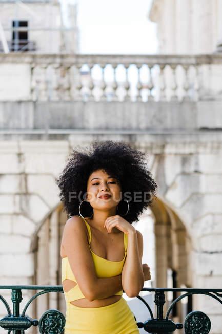 Mulher afro-americana atraente em terno amarelo em pé e olhando para a câmera no fundo urbano — Fotografia de Stock