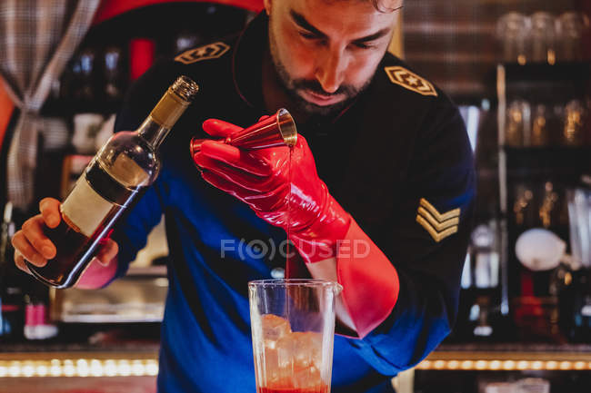 Barman in uniform and red glove preparing cocktail and concentrated on pouring drink to red bottle for mixing — Stock Photo
