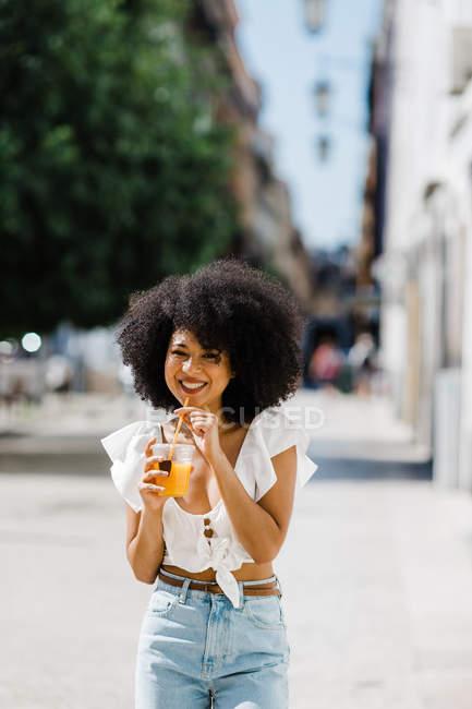 Alegre na moda afro-americana mulher bebendo suco de laranja e olhando para a câmera no fundo urbano — Fotografia de Stock